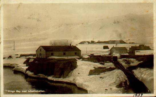 Picture side of real-photo postcard from 1939 at Kings Bay, Spitsbergen; illustration of the community there and the mooring mast for the Norge.